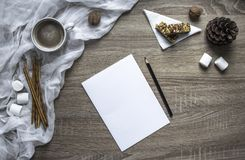 Auf einem hölzernen Hintergrund schreiben ein Blatt und ein Stift Eibische und Bonbons, ein Becher mit Kakao liegt ein geschmolze Stockfotografie