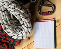 Auf einem hölzernen Hintergrund von Brettern, von Lügen ein großes Seil für das Klettern und von Karabiner, rote schöne Schuhe fü Lizenzfreie Stockbilder