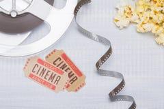 auf einem hellen Hintergrund, einem abgewickelten Film mit zwei Karten ins Kino und einem frischen Popcorn lizenzfreies stockbild