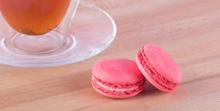 Auf einem hellen Holztisch sind eine Tasse Tee und eine Untertasse und ein Paar rosa Makkaroniplätzchen Stockfotos