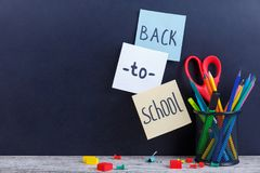 Auf einem Hintergrund mit der Aufschrift zurück zu Schule ist Bücher, Apfel, Bleistifte und ein Papierflugzeug Stockfoto