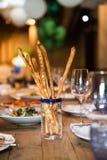 Auf einem Holztisch in einem Glas/Glas gibt es Grissini-Italiener Breadsticks Schön Siegeltabelle stockbild