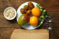 Auf einem Holztisch auf Orangen einer Weißplatte, Mango, eine Kiwilüge Horizontale Abbildung Beschneidungspfad eingeschlossen Lizenzfreie Stockfotografie