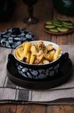 Auf einem Holztisch schnitt ein Teller von gebratenen Kartoffeln, im Hintergrund eine Platte mit frischen Gurken, †‹â€ ‹Scheibe stockfoto