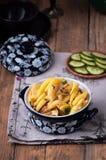 Auf einem Holztisch schnitt ein Teller von gebratenen Kartoffeln, im Hintergrund eine Platte mit frischen Gurken, †‹â€ ‹Scheibe stockbild