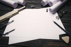 Auf einem Holztisch sind Zeichnungen, Kompassse, Bleistift, Gummiband, Machthaber und Bleistiftspitzer lizenzfreie stockfotografie