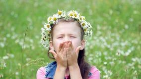 Auf einem Kamillenrasen ein süßes Mädchen in einem Kranz von den Gänseblümchen, lächelnd und drücken ihre Hände zu ihren Backen stock video footage