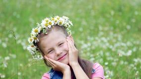 Auf einem Kamillenrasen ein süßes Mädchen in einem Kranz von den Gänseblümchen, lächelnd und drücken ihre Hände zu ihren Backen stock video