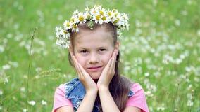 Auf einem Kamillenrasen ein süßes Mädchen in einem Kranz von den Gänseblümchen, lächelnd und drücken ihre Hände zu ihren Backen stock footage