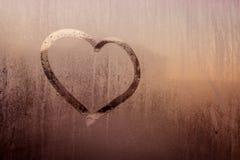 Auf einem nassen Glas wird ein Herz, ein Hintergrund der flockigen roten Farbe gezeichnet Lizenzfreies Stockbild