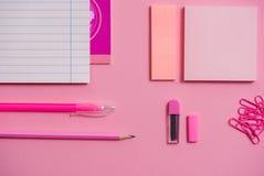 Auf einem rosa Hintergrund konkurrieren Schulzubehör und ein Stift, farbige Bleistifte, ein Zirkel, ein Zirkel, Kopienraum, Spitz Lizenzfreie Stockfotos