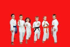 Auf einem roten Hintergrund in Kimono sechs führen Athleten Karatetechniken durch lizenzfreies stockfoto