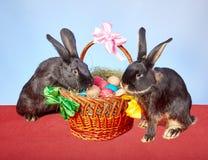 Auf einem roten Stoff der Korb mit Ostereiern und zwei Kaninchen Lizenzfreies Stockfoto