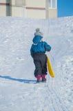 Auf einem schneebedeckten Hügel steigt das Kind Lizenzfreie Stockbilder