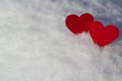 Auf einem schneebedeckten weißen Hintergrund seien Sie nahe bei zwei Valentinsgrüßen stockfoto