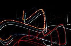 Auf einem schwarzen Hintergrund tanzen die glatten Linien des Lichtes der Nachtstadtmusik-Aufflackernlichter Lizenzfreie Stockfotos
