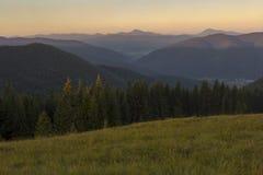 Auf einem sonnigen Sommertag, auf der Ansicht von der Hochebene zum Wald und auf den Bergen Blauer Himmel, viele grünes Gras und  Lizenzfreie Stockbilder