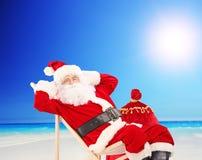 Auf einem Stuhl sitzende und, auf einem Strand entspannende Santa Claus Stockfotografie