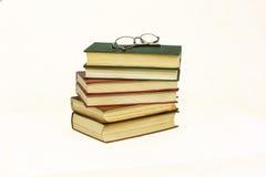 Auf einem weißen Hintergrund hält er einen Stapel Bücher und Gläser Stockfotos