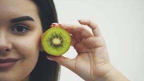 Auf einem weißen Hintergrund ein halbes Gesicht der jungen schönen Mädchennahaufnahme Hebt Hälfte Kiwi an und hebt sie zum Kopf a stock footage