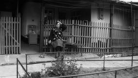 Auf einer Bank in einem Yard sitzt die Großmutter stock footage