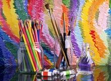 Auf einer dunklen Glastabelle sind Banken mit farbigen Bleistiften und Bürsten für das Zeichnen Stockbilder