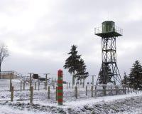 Auf einer Grenze: Stacheldraht, Wachturm Stockbild