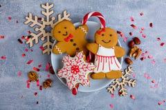 Auf einer Platte, dem Lebkuchen in Form eines kleinen Mannes und den Schneeflocken in der Zuckersüßen Glasur Ansicht von oben Stockbild