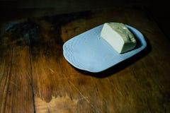 Auf einer Platte fetten Sie ein Stück Brot mit Öl ein lizenzfreie stockfotos