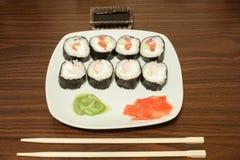 Auf einer Platte geschnittener Sushi Wasabi und in Essig eingelegter Ingwer, folgende Stöcke und Sojasoße Stockfotografie