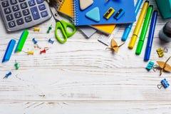 Auf einer weißen Tabelle in einer chaotischen Bestellungslüge: Taschenrechner, Gummiband, Büroklammern Zurück zu Schule-Hintergru stockbilder