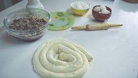 Auf einer weißen Tabelle eine Schüssel mit den Eiern und Mehl, bereit, oben gerollt zu werden und nahe bei dem Nudelholz Ansicht  Stockfoto
