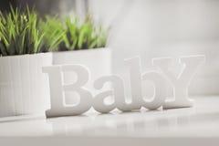 Auf einer weißen Tabelle gegen einen grünen Houseplant gibt es hölzerne Buchstaben mit einem Aufschrift Baby stockbild