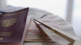 Auf einer weißen Tabelle gibt es viel Geld, einen Pass und ein kleines Flugzeug, die vom Geld hergestellt werden Das Konzept des  stock video
