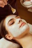 Auf Gesicht der Frau wendet Kosmetiker eine Maske im Badekurortsalon an Lizenzfreies Stockbild