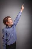 Auf grauem Hintergrund hob Junge seine Hand oben an Lizenzfreies Stockfoto