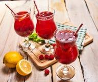 Auf hölzernem sind eiskaltes Getränkeglas mit Beerencocktail Stockfoto