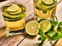 Auf hölzernen Brettern sind Gläser mit grünem transparentem Getränk Stockbilder