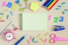 Auf Lügen eines Beigehintergrundes ein leeres Notizbuch mit einem Platz für Aufschriften Um es sind verschiedene farbige Bleistif Lizenzfreie Stockfotografie