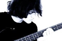 Auf lagerfotographie: Junges jugendlich-Junge, der Baß-Gitarre spielt Lizenzfreies Stockbild