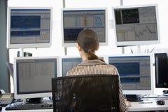 Auf lagerhändler, der mehrfache Überwachungsgeräte betrachtet Stockfoto