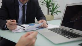 Auf Laptop im Büro veranschlagen Geschäftsleute die Grafiken am Desktop stock video