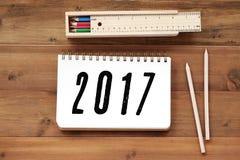 2017 auf Notizbuchpapier, -kasten und -bleistift auf hölzernem Hintergrund Stockfotografie