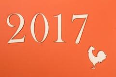 2017 auf orange Hintergrund Jahr des Hahnes Stockfotografie