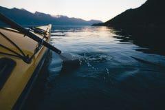 Auf ruhigem Wasser mit Bergen im Hintergrund allein Kayak fahren während Sonnenuntergang lizenzfreies stockfoto