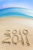 Auf Sand am Ozeanrand wird es 2010-2011 geschrieben Stockfoto