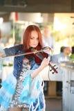 Auf schönem, schwachem und schlankem Mädchen des Stadiums - mit dem brennenden roten Haar - ein weithin bekannter Musiker, Virtuo Lizenzfreie Stockfotos