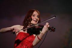 Auf schönem, schwachem und schlankem Mädchen des Stadiums - mit dem brennenden roten Haar - ein weithin bekannter Musiker, Virtuo Stockfotos