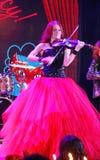 Auf schönem, schwachem und schlankem Mädchen des Stadiums - mit dem brennenden roten Haar - ein weithin bekannter Musiker, Virtuo Stockfotografie