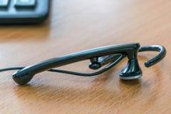 Auf Schreibtisch verdrahteten die Lügen Kopfhörer und im Hintergrund liegt der Taschenrechner Lizenzfreies Stockbild